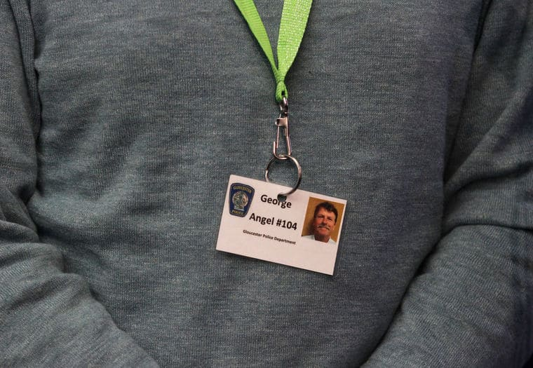 """MIKE SPRINGER/Staff photo George Hackford of Gloucester wears a card identifying him as """"Angel #104"""" during a press conference Tuesday with Gloucester police Chief Leonard Campanello at police headquarters in Gloucester. Hackford was the """"angel"""" assigned to help the first person who took up Campanello's offer of help, rather than arrest, for any drug addict turning himself in."""