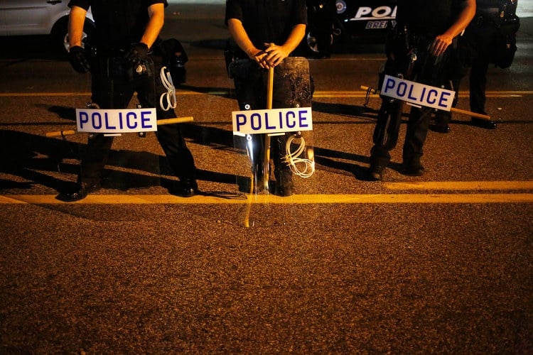 Police officers holding riot shields and wooden batons stand and watch protesters during a night time demonstration in Ferguson, Missouri, on Aug. 19, 2014. Photographer: Luke Sharrett/Bloomberg