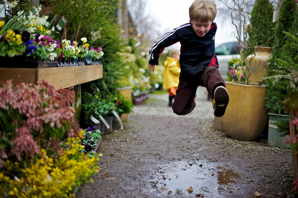 A child jumping a puddle